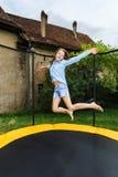 Adolescente lindo que salta en el trampolín Imagenes de archivo