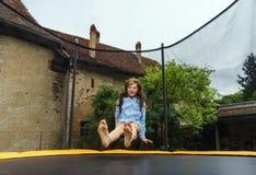 Adolescente lindo que salta en el trampolín Imagen de archivo