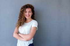 Adolescente lindo que se coloca con los brazos cruzados y la sonrisa Imagenes de archivo