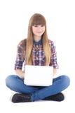 Adolescente lindo que se sienta con el ordenador portátil aislado en blanco Imagenes de archivo