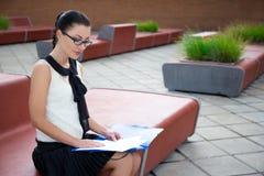Adolescente lindo que se sienta en banco y que lee algo Foto de archivo libre de regalías