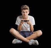 Adolescente lindo que se sienta en el piso que juega videojuegos Imagenes de archivo