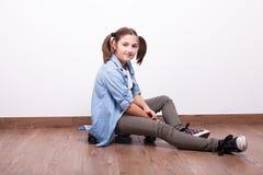Adolescente lindo que se sienta en un monopatín Foto de archivo libre de regalías