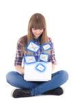 Adolescente lindo que sienta y que envía mensajes con isola del ordenador portátil Fotos de archivo libres de regalías
