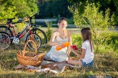 Adolescente lindo que tiene comida campestre con la madre en campo en la puesta del sol Foto de archivo