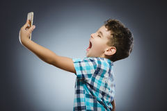 Adolescente lindo que toma el selfie en fondo gris Fotos de archivo libres de regalías