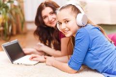 Adolescente lindo que usa el ordenador portátil con su madre Imagenes de archivo
