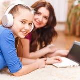 Adolescente lindo que usa el ordenador portátil con su madre Imágenes de archivo libres de regalías