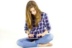 Adolescente lindo que usa la tableta que mira la cámara aislada Fotos de archivo libres de regalías