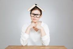 Adolescente lindo serio en vidrios con el libro en la cabeza Imágenes de archivo libres de regalías