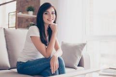Adolescente lindo sonriente acertado se está sentando en el sofá acogedor en sitio S Fotografía de archivo libre de regalías