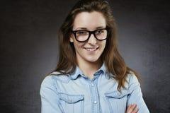 Adolescente lindo sonriente en vidrios nerdy Imagen de archivo libre de regalías