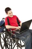Adolescente lisiado usando el ordenador Fotografía de archivo