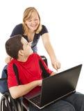 Adolescente lisiado y amigo en el ordenador Fotos de archivo