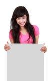 Adolescente llevando a cabo encendido a la tarjeta en blanco Fotografía de archivo
