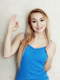 Adolescente louro da mulher que mostra o sinal aprovado da mão do sucesso Imagem de Stock