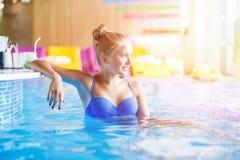 Adolescente magnífico que se sienta en piscina cerca de la barra Foto de archivo libre de regalías