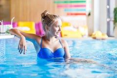 Adolescente magnífico que se sienta en piscina cerca de la barra Imagenes de archivo