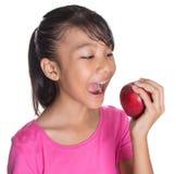 Adolescente malayo asiático joven que come Apple rojo I Foto de archivo libre de regalías