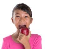 Adolescente malayo asiático joven que come Apple rojo III Foto de archivo libre de regalías