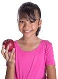Adolescente malayo asiático joven que come Apple rojo VIII Imágenes de archivo libres de regalías