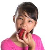Adolescente malayo asiático joven que come Apple rojo X Imagenes de archivo