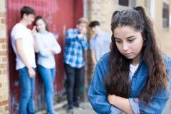Adolescente malheureuse bavardé environ par des pairs images stock