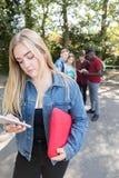 Adolescente malheureuse intimidé par le message textuel à l'école photos stock
