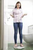 Adolescente malheureuse se tenant sur des échelles de salle de bains Image libre de droits