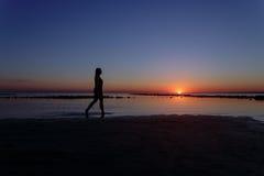 Adolescente marchant dans l'eau sur la plage dans le coucher du soleil Images stock