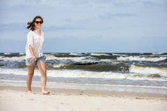 Adolescente marchant sur la plage Images stock