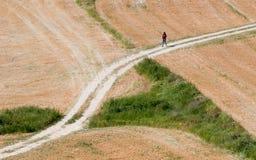 Adolescente marchant sur une route de campagne Images libres de droits