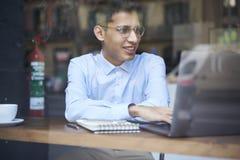 Adolescente maschio sorridente in occhiali che guarda video divertente nelle reti sociali Immagine Stock