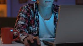 Adolescente masculino adicto en las auriculares que juegan al juego online en la noche, comportamiento nervioso almacen de video
