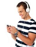 Adolescente masculino con el jugador mp3 y los earbuds Fotos de archivo