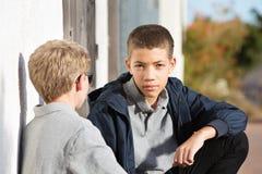 Adolescente masculino con la expresión seria que escucha el amigo Fotos de archivo