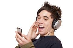 Adolescente masculino con los auriculares que escucha la música Fotos de archivo