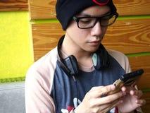 Adolescente masculino de la cadera que usa un smartphone Fotografía de archivo