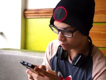 Adolescente masculino de la cadera que usa un smartphone Foto de archivo
