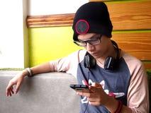 Adolescente masculino de la cadera que usa un smartphone Fotos de archivo libres de regalías