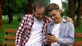 Adolescente masculino e paizinho que olham o vídeo engraçado no smartphone, no riso e no sorriso fotografia de stock royalty free