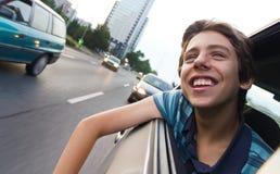 Adolescente masculino en coche que disfruta de la opinión de la ciudad Imagen de archivo libre de regalías