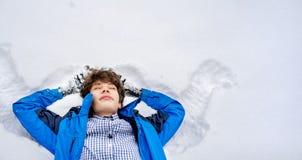 Adolescente masculino joven en la mentira casual en la nieve en un día de invierno f foto de archivo libre de regalías