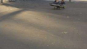 Adolescente masculino que aprende mantener el equilibrio, monopatín que monta, actividades al aire libre almacen de metraje de vídeo