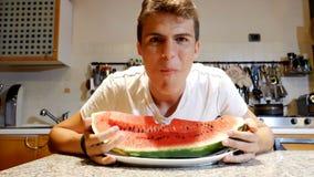 Adolescente masculino que come a melancia em casa vídeos de arquivo