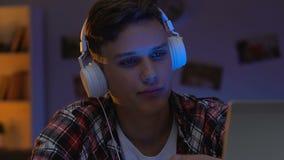 Adolescente masculino que enrola redes sociais no portátil na noite, tabela de assento da casa video estoque
