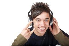 Adolescente masculino que escucha la música y las sonrisas felices Imágenes de archivo libres de regalías