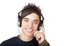 Adolescente masculino que escucha la música y las sonrisas felices Imagen de archivo