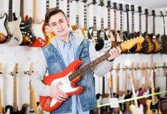 Adolescente masculino que examina las guitarras eléctricas Imágenes de archivo libres de regalías