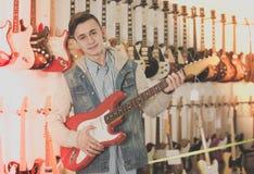 Adolescente masculino que examina las guitarras eléctricas Foto de archivo libre de regalías